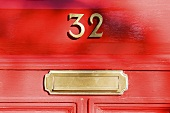 A red front door with a house number and a letter box