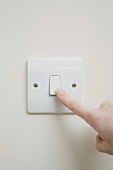 A finger on a light switch