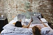 A couple reading newspapers in bed