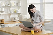 A young woman with laptop sitting on a kitchen counter