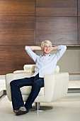 A middle aged man relaxing in a modern armchair