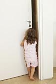 A young girl pushing open a door