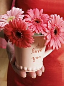 "Hand holding ""I love you"" cup with flowers"