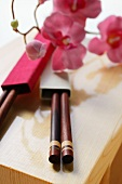 Japanese chopsticks and flowers on wooden board
