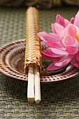 Chopsticks in woven wrapper with water lily on plate