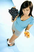 Young woman standing on scales with crisps and grapes
