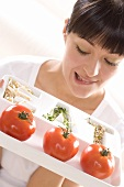 Young woman holding a plate of tomatoes and sprouts