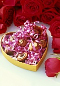 Chocolates in heart-shaped box, red roses