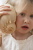 Girl listening to a shell in wonderment