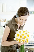 Young woman with white narcissi in kitchen