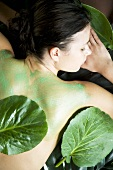 Young woman with body mask and leaves on her back