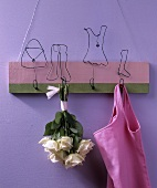 Wall-mounted coat rack with amusing wire figures