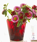 Asters and sweet williams in red glass vase