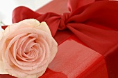Gift in red wrapping paper with ribbon and rose (close-up)