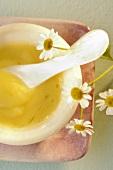 Kamillencreme und frische Kamillenblüten (Ausschnitt)