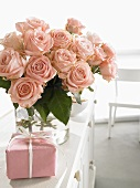 Vase of pink roses and wrapped gift for Mother's Day