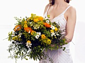 Woman holding bouquet of marigolds and ranunculus