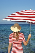 Woman in hat with red and white sunshade by the sea