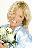Smiling woman holding bouquet of white roses in her hands