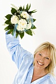 Smiling woman holding bouquet of white roses