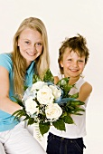 Two children holding bouquet of white roses in their hands