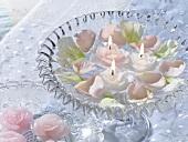 Blüten und Schwimmkerzen in einer Glasschale