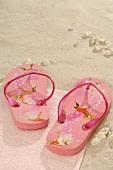 Pink flip-flops on a towel on sand