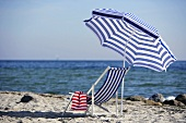 Blue and white deckchair and beach umbrella by the sea