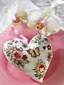 Padded heart in patterned fabric with hanging loop on plate