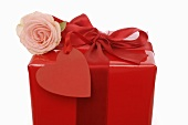 Gift in red wrapping paper with rose