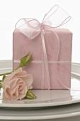 Rosa Geschenk und Rose auf einem Teller