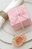 Place-setting with gift in pink wrapping paper