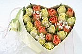 Heart-shaped box full of roses and gypsophila