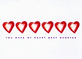 Red hearts and the words, 'You make my heart beat shorter' (print)