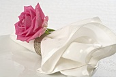 Fabric napkin with pink rose on white plate