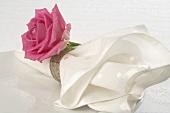Stoffserviette mit pinkfarbener Rose auf weißem Teller