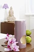 Duftlampe mit Limetten und Orchideenblüten