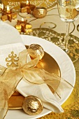 Place-setting with napkin, gold bow and gilded walnut