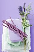 Incense sticks & bars of soap on towel, sprig of lavender