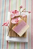 Soap and flowers on wooden soap dish on towel
