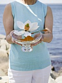 Woman holding glass dish of flowers, sea in background