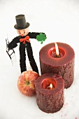 Chimney sweep, apple and red candles in snow
