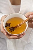 Woman holding bowl of tea with star anise & cinnamon stick