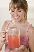 Woman holding jug of fruit juice with ice cubes