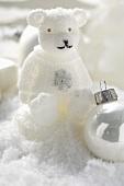 Christmas decoration: polar bear & Christmas baubles in snow