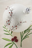White Christmas tree bauble on embroidered linen cloth