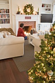Woman by fireplace in living room decorated for Christmas