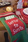 Stocking with letter to Santa Claus, beside Xmas place-setting