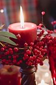 Rote Kerze mit Beerendeko