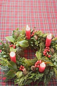 Advent wreath with four burning candles on checked cloth